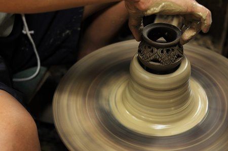 Artist shaping a bowl on a pottery wheel  Stock Photo