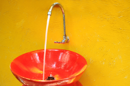 Red sink on yellow wall  Stock Photo