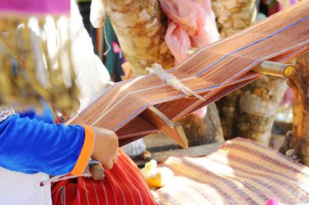 Hill tribe women were sitting weaving.
