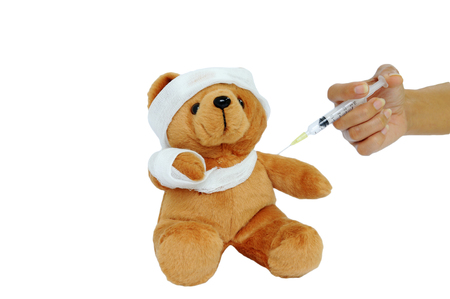 injected: Bear doll with gauze wrapped the head, arms and are being injected.