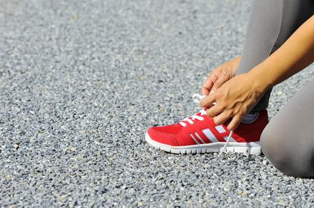 shoelaces: Female hand tying shoelaces on footpath.
