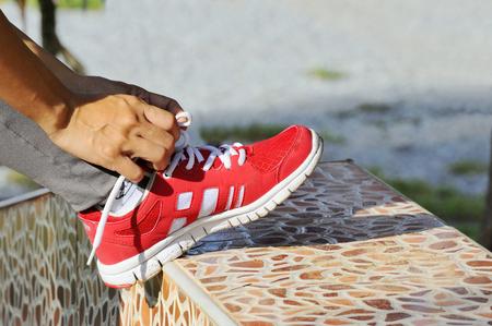 Female hand tying shoelaces on footpath.