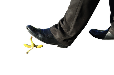 tripping: Business man walk over a banana peel.