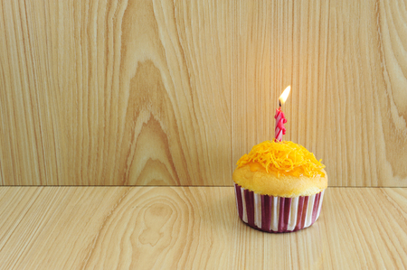 Golden cupcake and birthday candle