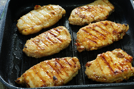 Sliced pork grilled on a pan with olive oil.