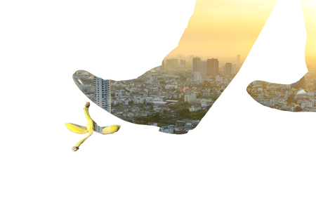 Double exposure of businessman walk over a banana peel and city image