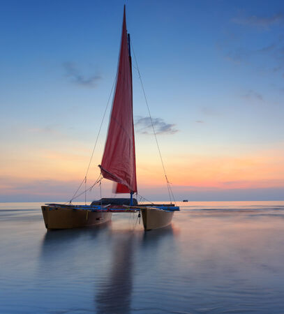 murk: Red sailboat on the beach with a beautiful sunset Stock Photo