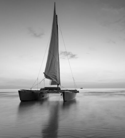 murk: sailboat on the beach with a beautiful sunset in black and white Stock Photo