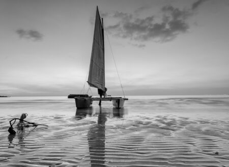 reflexive: sailboat on the beach with a beautiful sunset in black and white Stock Photo