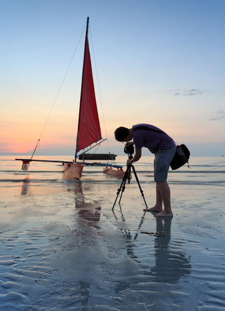 Photographer is taking a photo of a sailboat photo