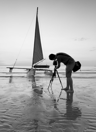 reflexive: Photographer is taking a photo of a sailboat in black and white Stock Photo