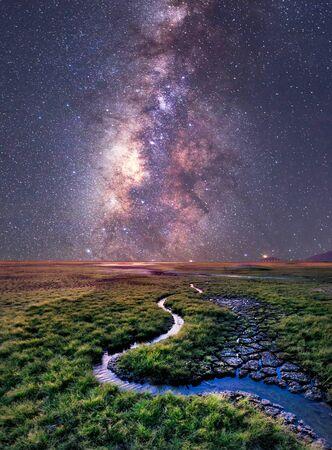 La Vía Láctea se eleva sobre el campo de hierba, Tailandia
