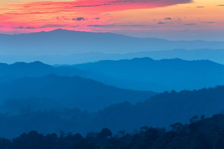 generic location: Layer of mountains in the mist at sunset time with burning sky, Nan Province, Thailand Stock Photo