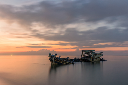 insides: An old shipwreck or abandoned shipwreck taken during a beautiful sunset , Wrecked boat abandoned stand on beach or Shipwrecked off the coast of Thailand.