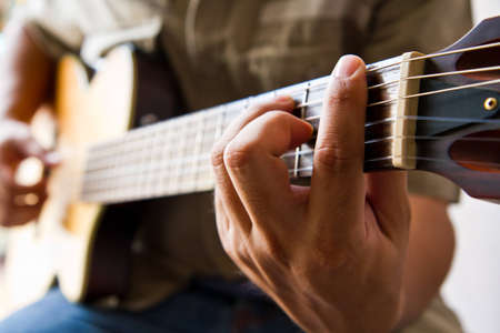Man playing a guitar F chord  photo