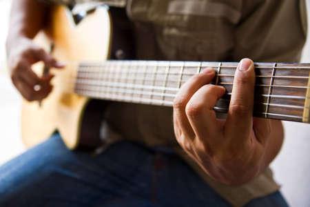 Man playing a guitar F  chord  photo