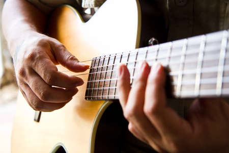 Man playing a guitar picking style  photo