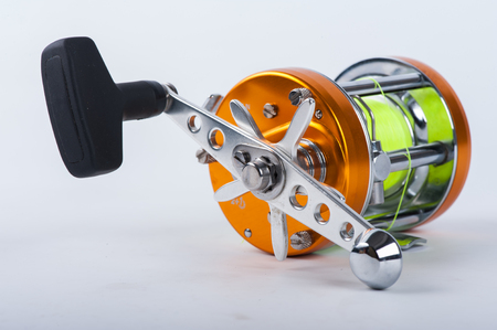 the fishing reel for fishing isolated over white photo
