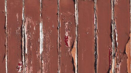 The old brown lath wall that has faded from the sun for a long time.
