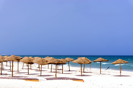 Landscape of empty beach covered with umbrellas in Sousse, Tunisia.