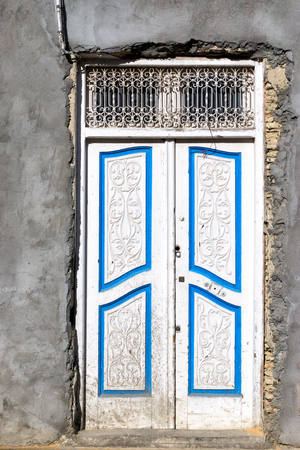 White door and grey facade of house in Kairouan, Tunisia. Фото со стока