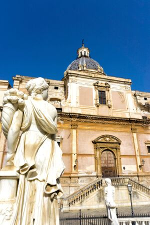 View of woman sculpture with the Saint Catherine Church in the background in Palermo, Italy