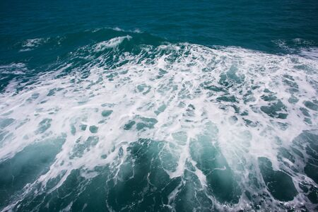 Waves, foam and wake caused by cruise ship in the sea.