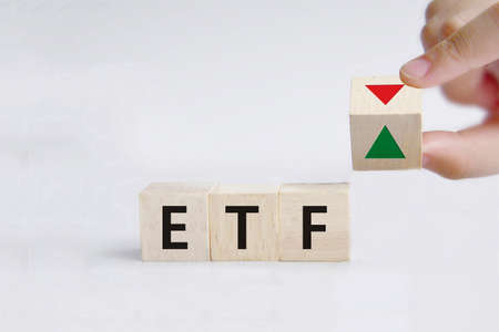 Hand is turning a dice and changes the direction of an arrow symbolizing that the value of an ETF (Exchange Traded Fund) is going up (or vice versa) Stock fotó