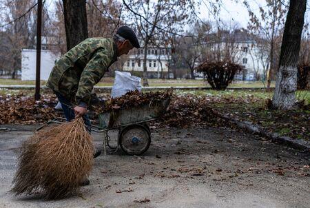 Janitor sweeping a broom yard.Janitor sweeping a broom yard Foto de archivo