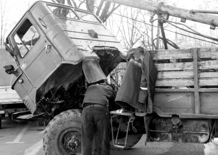Man repairs a truck by lifting a cab