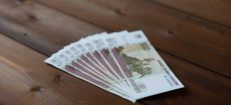 Banknotes are located on a wooden background.