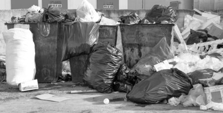 Garbage cans and trash. Black and white photo.