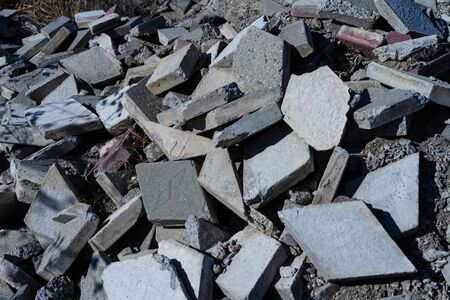 A pile of broken street tiles with cement and sand