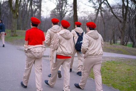 Guys in red berets walk down the street