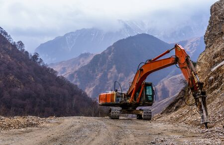 Excavator crushes stones in the mountains Stock Photo