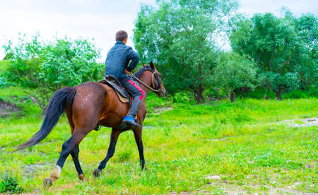 A boy rides on the ground riding a horse