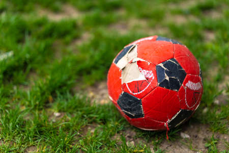 A torn soccer ball lies on the grass Imagens