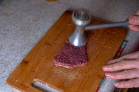 Beating a piece of meat for frying