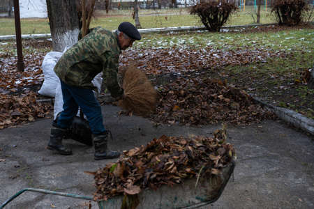 A man cleans and sweeps a yard