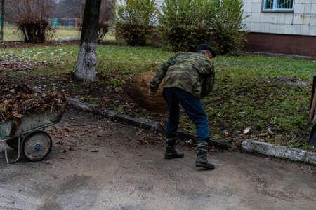 Janitor sweeping a broom yard Foto de archivo