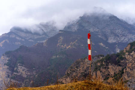 Weather vane on a background of mountains with fog and clouds above them