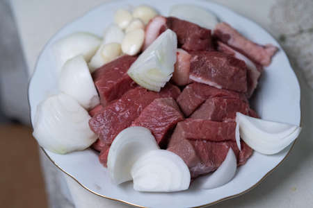 Sliced ​​pieces of meat are on a plate for further cooking