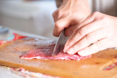 Cut a piece of meat with a knife Stock fotó