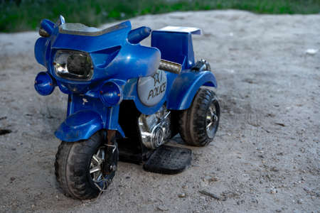 Children's motorcycle stands in the sand
