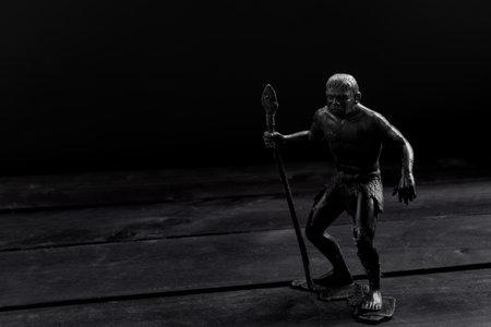 Figurine of primitive man, on wooden background