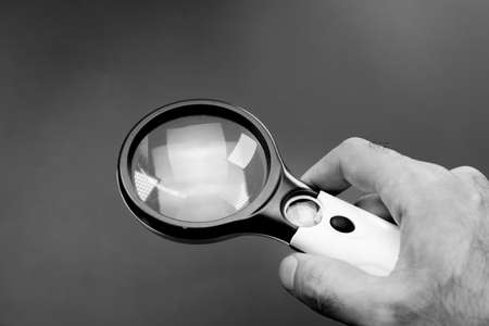 Magnifying glass in the hands of a man