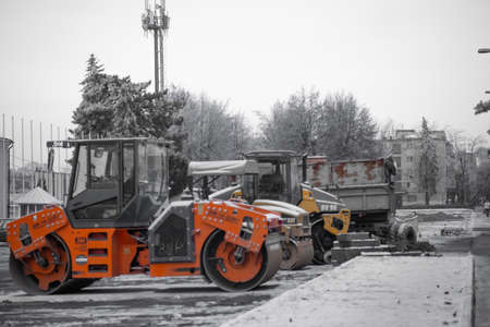 Heavy vehicles for road repairs stand in winter Imagens