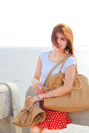 brown leather hat: Happy lady at the beach with her brown hat and leather bag