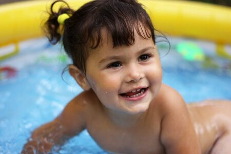 blow up: portrait of a happy smiling little girl in a blow up swimming pool