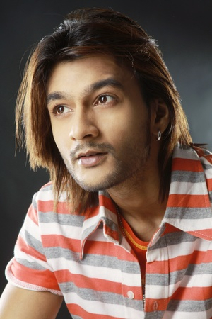 Close-up image of a attractive Indian male with long hair, looking away. photo
